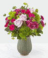 When you need to say a little more, say it with the Abundance Bouquet. Comprised of lavender roses surrounded by vibrant greens and purples, the beauty of this bouquet is just bursting right out of a muted green ceramic vase with a gold metallic finish.