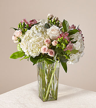 White hydrangea, yellow roses, peach spray roses, and pink alstroemeria in a clear glass vase with a gold base